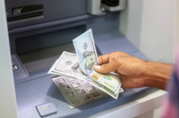 A man withdraws US dollars from a Bank of Maldives Dollar ATM. PHOTO: NISHAN ALI / MIHAARU