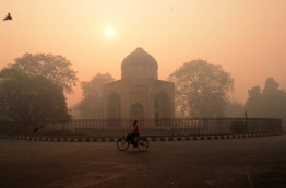 """An Indian cyclist rides along a street as smog envelops a monument in New Delhi on October 31, 2016, the day after the Diwali festival. New Delhi was shrouded in a thick blanket of toxic smog a day after millions of Indians lit firecrackers to mark the Diwali festival, causing the air pollution to hit """"severe"""" level. The pollutants breached the 1000 microgram mark in the Indian capital and shot up nearly 10 times above the normal level in  the early hours of Monday, mostly owing to bursting of millions of firecrackers, according to a weather scientist.  / AFP PHOTO / MONEY SHARMA"""