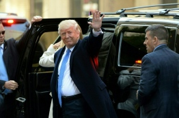 Republician presidential nominee Donald Trump waves as he arrives at a polling station in New York where Trump was to cast his ballot, November 8, 2016. / AFP PHOTO / Robyn Beck