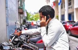 A man speaks on the phone. PHOTO: HUSSAIN WAHEED / MIHAARU