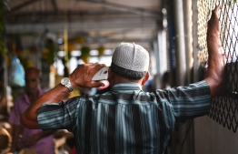 A senior citizen speaking on the phone inside a local market stall. PHOTO: MIHAARU
