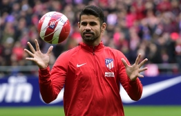 Atletico Madrid's Spanish forward Diego Costa catches a ball at the start of a training session following his welcoming ceremony at the Wanda Metropolitan Stadium in Madrid on December 31, 2017. / AFP PHOTO / PIERRE-PHILIPPE MARCOU