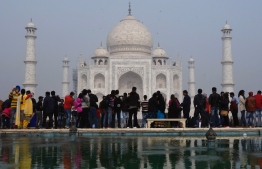 Crowds gather to visit the Taj Mahal in Agra on January 3, 2018. / AFP PHOTO / DOMINIQUE FAGET