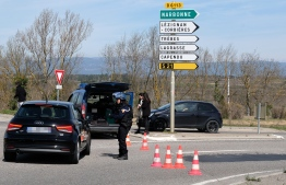 French gendarmes block the access to Trebes, where a man took hostages at a supermarket on March 23, 2018 in Trebes, southwest France. At least one person was feared dead after a gunman claiming allegiance to the Islamic State group fired shots in a hostage-taking at a supermarket in southwest France, police said. / AFP PHOTO / ERIC CABANIS At least one person was feared dead after a gunman claiming allegiance to the Islamic State group fired shots in a hostage-taking at a supermarket in southwest France, police said. / AFP PHOTO / ERIC CABANIS