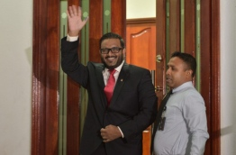 Former VP Adheeb waves as he is led out of the Criminal Court after he was sentenced to 10 years in prison on terror charges. MIHAARU PHOTO/ MOHAMED SHARUHAAN
