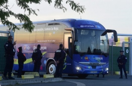 Policemen stand guard as the bus of the Spanish national football team leaves La Rochelle's airport on June 8, 2016, after the team's arrival for the Euro 2016 football tournament. / AFP PHOTO
