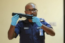 A police officer displace a weapon that was recovered from a stash found in an uninhabited island. PHOTO/RAAJJE.MV