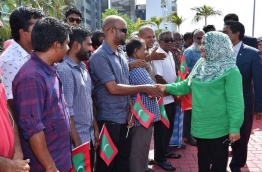 First Lady Fathimath Ibrahim shakes hands with party supporters gathered near the jetty as she arrived from an official trip to Malaysia with her husband. MIHAARU FILE PHOTO/MOHAMED SHARUHAAN