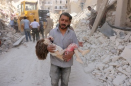 EDITORS NOTE: Graphic content / A Syrian man carries the body of a child following a reported Syrian government forces bombing at the Tariq al-Bab neighbourhood in the rebel-held area of the northern city of Aleppo on June 20, 2016.The Syrian war has killed more than 280,000 people./ AFP PHOTO / THAER MOHAMMED