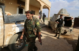 US-backed Kurdish and Arab fighters advance into the Islamic State (IS) jihadist's group bastion of Manbij, in northern Syria, on June 23, 2016.Backed by air strikes by the US-led coalition bombing IS in Syria and Iraq, fighters with the Syrian Democratic Forces (SDF) alliance entered Manbij from the south, a monitoring group said./ AFP PHOTO / DELIL SOULEIMAN