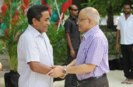 Former president Gayoom (R) shakes the hand of his half brother and incumbent president Yameen at a ceremony. FILE PHOTO/PRESIDENT'S OFFICE