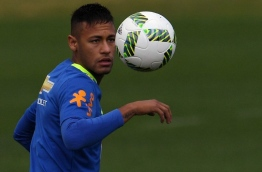 Brazilian footballer Neymar eyes the ball during a training session ahead of the Rio 2016 Olympic Games, at the Granja Comary sports complex in Teresopolis, about 90 km from Rio de Janeiro, Brazil, on July 19, 2016. / AFP PHOTO / VANDERLEI ALMEIDA