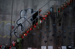 A man lights candles on the stairways near the Love Parade Memorial located at the site of the accident that left 21 people dead on 24 July 2010, in Duisburg, Germany, 24 July 2016. / AFP PHOTO / PATRIK STOLLARZ