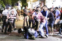 Protesters beating the police officer during the May Day protest last year.