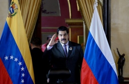 Venezuelan President Nicolas Maduro waves as he arrives for the signing of agreements with Russian oil company Rosneft's CEO, Igor Sechin (out of frame) at Miraflores presidential Palace in Caracas on July 28, 2016. / AFP PHOTO / FEDERICO PARRA