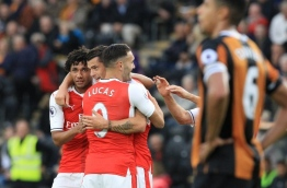 Arsenal's Swiss midfielder Granit Xhaka (C) celebrates with Arsenal's Egyptian midfielder Mohamed Elneny (L) after scoring their fourth goal during the English Premier League football match between Hull City and Arsenal at the KCOM Stadium in Kingston upon Hull, north east England on September 17, 2016. / AFP PHOTO / Lindsey PARNABY