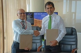 Dhiraagu's CEO Ismail Rasheed (L) and economic minister Mohamed Saeed sign the agreement appointing Dhiraagu as platinum sponsor of Maldives Investment Forum 2016. PHOTO/DHIRAAGU