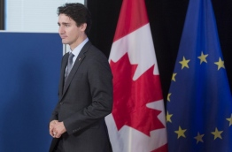 Canadian Prime Minister Justin Trudeau and European Union leaders on October 30, 2016 finally signed a landmark trade deal seven years in the making, after it was nearly being torpedoed by a small region of Belgium. CETA removes 99 percent of customs duties between the two sides, linking the single EU market with the world's 10th largest economy. / AFP PHOTO / POOL / Thierry MONASSE