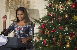 """First Lady Michelle Obama speaks during the unveiling of the 2016 holiday decorations in the theme of """"The Gift of the Holidays,"""" in the East Room of the White House in Washington, DC, November 29, 2016. / AFP PHOTO / SAUL LOEB"""