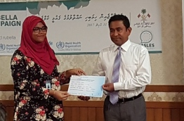 President Yameen awarding a certificate for President Office staff who got vaccinated PHOTO:President Office