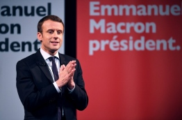 """French presidential election candidate for the En Marche movement Emmanuel Macron gestures as speaks during an event organised by the collective """"Elles Marchent"""" (They Walk in feminine in French), during International Women's Day on March 8, 2017, in Paris. / AFP PHOTO / Eric FEFERBERG"""