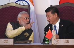 Indian Prime Minister Narendra Modi speaks with Chinese President Xi Jinping. PHOTO: AFP