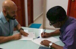 """A photo released by the opposition, depicting Isdhoo MP Ahmed """"Gaari"""" Rasheed (R) pictured signing the alleged petition to file a motion of no confidence against Parliament Speaker Abdulla MAseeh"""