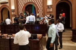 Security forces remove opposition lawmakers gathered at the parliament speaker's table while lawmaker protest.