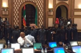 Security forces gathered around the speaker's table in the parliament chambers while opposition lawmakers protest.