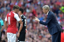 Arsenal's French manager Arsene Wenger (R) interacts with Arsenal's German midfielder Mesut Ozil during the pre-season friendly football match between Arsenal and Sevilla at The Emirates Stadium in north London on July 30, 2017, the game is one of four matches played over two days for the Emirates Cup. / AFP PHOTO / OLLY GREENWOOD