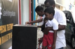 A boy puts money in a fund box placed by Raajje TV to raise aid for the persecuted Rohingya Muslims of Myanmar. PHOTO/TWITTER