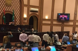 """Speaker Abdulla Maseeh addresses the first sitting of 2017's third term of the parliament from his elevated seat behind a wooden """"wall"""", while opposition lawmakers protest and call on him to step down. PHOTO/MAJLIS"""