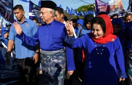 Malaysia's Prime Minister Najib Razak (C) and his wife Rosmah Mansor wave to their supporters as they arrive at the nomination centre to hand over election documents in Pekan on April 28, 2018. Malaysia's 14th general election will be held on May 9 with nominations taking place on April 28. / AFP PHOTO / Mohd RASFAN