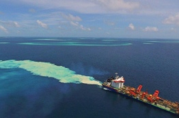 Aerial view of a dredger reclaiming a lagoon in Kaafu atoll.