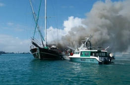 An MNDF vessel approaches the safari yacht which caught fire in Hulhumale harbour to put out the flames. PHOTO/READER