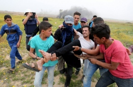 Palestinian men help evacuate an injured protester during clashes with Israeli troops near Khan Yunis by the border fence between Israel and the southern Gaza Strip on March 23, 2018. / AFP PHOTO / SAID KHATIB
