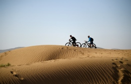 Competitors push their bikes along a sand dune during Stage 4 of the 13th edition of the Titan Desert 2018 mountain biking race between Boumalne Dades and Merzouga in Morocco on May 2, 2018. The Titan Desert 2018 is 600 kilometre mountain bike race completed over six days, snaking between Boumalne Dades, at the foot-slopes of the High Atlas summits, and Erfoud, an oasis town in the Sahara Desert.