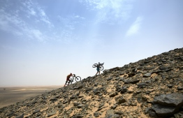 Competitors push and carry their bikes up a sand dune during Stage 5 of the 13th edition of Titan Desert 2018 mountain biking race around Merzouga in Morocco on May 3, 2018. The Titan Desert 2018 is 600 kilometre mountain bike race completed over six days, snaking between Boumalne Dades, at the foot-slopes of the High Atlas summits, and Erfoud, an oasis town in the Sahara Desert.