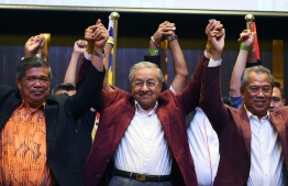 Former Malaysian prime minister and opposition candidate Mahathir Mohamad (C) celebrates with his coalition leaders during a press conference in Kuala Lumpur on early May 10, 2018.  Malaysia's opposition alliance headed by veteran ex-leader Mahathir Mohamad, 92, has won a historic election victory, official results showed on May 10, ending the six-decade rule of the Barisan Nasional (BN) coalition.  / AFP PHOTO / Manan VATSYAYANA