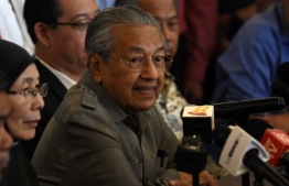 """Former Malaysian prime minister and winning opposition candidate Mahathir Mohamad (C) speaks to journalists during a press conference in Kuala Lumpur on May 10, 2018. Malaysian veteran ex-leader Mahathir Mohamad, 92, said he expected to be sworn in as prime minister later May 10 after his stunning election win, adding there was an """"urgency"""" for him to take office.  / AFP PHOTO / ROSLAN RAHMAN"""
