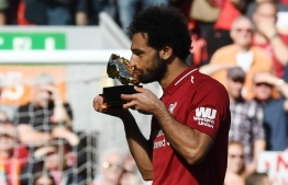 Liverpool's Egyptian midfielder Mohamed Salah celebrates after being awarded the golden boot award for most goals scored in the season after the English Premier League football match between Liverpool and Brighton and Hove Albion at Anfield in Liverpool, north west England on May 13, 2018. / AFP PHOTO / Paul ELLIS / RESTRICTED TO EDITORIAL USE. No use with unauthorized audio, video, data, fixture lists, club/league logos or 'live' services. Online in-match use limited to 75 images, no video emulation. No use in betting, games or single club/league/player publications.  /