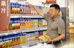 A customer selects imported juice at a store in Qingdao in China's eastern Shandong province on May 24, 2018.  China said on May 24 it has not set a target to cut its trade surplus with the US but will seek to increase imports after the two sides stepped back from a potential trade war. / AFP PHOTO / - /