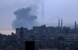 A picture taken early on June 3, 2018 from Gaza City shows smoke plumes rising after an Israeli air strike in Beit Lahia in the northern Gaza Strip. Israeli aircraft pounded over a dozen militant targets in Gaza, the army said on June 3, after Palestinian projectile fire shattered a ceasefire reached just days prior following the worst flare-up since the 2014 war. / AFP PHOTO / Mahmud Hams