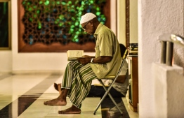 An elderly man recites Quran after prayers in the peaceful vicinity of The Grand Friday Mosque, located in the capital city's Islamic Centre. PHOTO: AHMED NISHAATH / MIHAARU