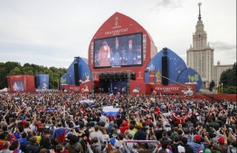 People watch the opening ceremony ahead of the Russia 2018 World Cup Group A football match between Russia and Saudi Arabia in the fan zone near the main building of the Moscow State University in Moscow on June 14, 2018. / AFP PHOTO / Maxim ZMEYEV