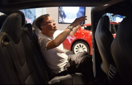 "(FILES) This file photo taken on May 23, 2018 shows a man taking a photo inside a Tesla Model X in a Tesla showroom in Beijing China on June 15, 2018 swiftly retaliated by imposing ""equal"" tariffs on US products following a decision by US President Donald Trump to slap duties on $50 billion of Chinese products. / AFP PHOTO / GREG BAKER"