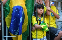 A young fan of Brazil attends the broadcasting of the World Cup 2018 football match against Switzerland, during a public event in the Alzirao neighbourhood of Rio de Janeiro on June 17, 2018. PHOTO: CARL DE SOUZA / AFP