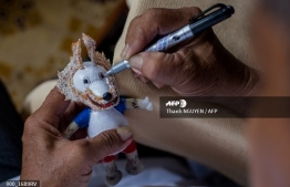 This picture taken on June 20, 2018 shows retired Vietnamese English teacher Nguyen Thanh Tam painting an eggshell as he creates a model of Zabivaka, the 2018 Russian World Cup mascot, at his home in Ho Chi Minh City. Tam, 67, spends hours every day making the models, driven by his football fanaticism -- a passion shared by millions across Vietnam glued to the 2018 Football World Cup matches since the tournament kicked off in Russia on June 14. Thanh NGUYEN / AFP