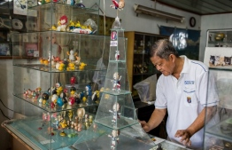 This picture taken on June 20, 2018 shows retired Vietnamese English teacher Nguyen Thanh Tam displaying an Eiffel Tower glass case containing models of Super Victor, the Euro 2016 football mascot, made from eggshell, at his home in Ho Chi Minh City.  Tam, 67, spends hours every day making the models, driven by his football fanaticism -- a passion shared by millions across Vietnam glued to the 2018 Football World Cup matches since the tournament kicked off in Russia on June 14. / AFP PHOTO / Thanh NGUYEN