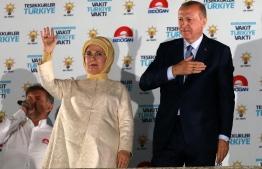 Turkish President Tayyip Erdogan and his wife Emine Erdogan greet supporters at the AKP headquarters in Ankara, Turkey June 25, 2018. / AFP PHOTO / Adem ALTAN